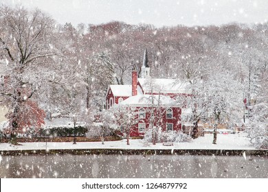 Beautiful rural winter scene with church, trees, pond with falling snow