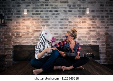 Beautiful Russian blonde girl in causal clothes playing music on guitar for freaky man in comical mask. Unusual couple spend time together in stylish apartment. Unicorn with girlfriend at home