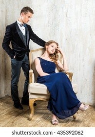 Beautiful Russian couple: a young man in a tuxedo with a bow tie and a girl in an elegant evening dress