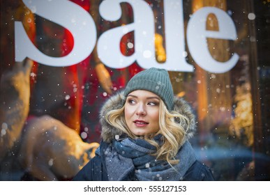 "Beautiful Russian girl came into the store on sale and is photographed on a background of the inscription ""sale""."