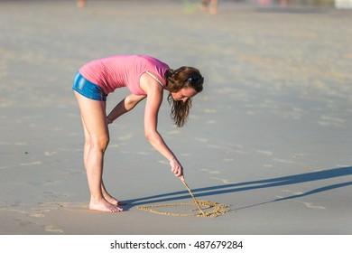 Beautiful Russian girl draws in the sand beach paradise
