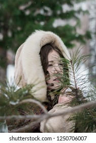 Beautiful Russian girl in a fur coat in the winter playing hide and seek.