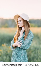 Beautiful Russian girl in a hat and summer dress, walking on the field in the grass to the waist. Happy traveler, collecting herbs, smiling. Sunset in the forest.