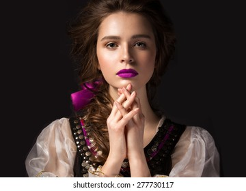 Beautiful Russian girl in national dress with a braid hairstyle and pink lips. Beauty face. Picture taken in the studio on a black background.