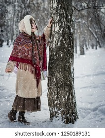 Beautiful Russian girl in a scarf in the winter playing hide and seek.