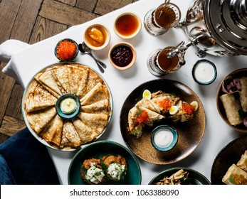 beautiful russian pancakes (blini) with different toppings on the table:  caviar, honey, sourcream, jams. Russian cuisine, horizontal photo, top view