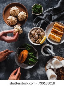 Beautiful Russian Vareniki or Pelmeni Dough (Russian Pierogi), fried crepes and Chicken Kiev and Georgian khinkali on a plates. Male hand holding a  khinkali. concrete background, vertical