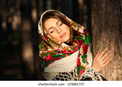 Beautiful Russian village girl in headscarves near the tree in the forest