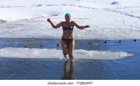 A beautiful Russian woman is bathed in icy water. Winter holidays in Siberia.