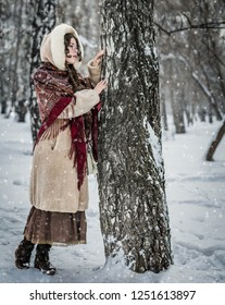 Beautiful Russian woman in a scarf in winter playing hide and seek.