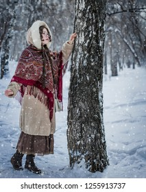 Beautiful Russian woman in a scarf in the winter playing hide and seek.