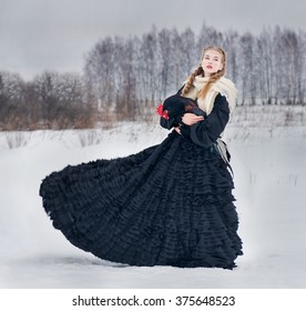 Beautiful Russian woman in a traditional dress. Russian village. Winter.