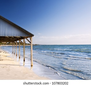 Beautiful and rustic beach shed / shelter on the beach at the water line.
