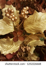Beautiful rustic Christmas floral arrangement with shiny gold berries, leaves and burgundy flowers.