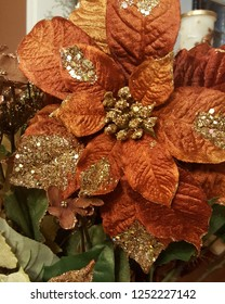 Beautiful rustic Christmas floral arrangement with burgundy poinsettia, gold berries, and glittering leaves.