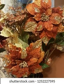 Beautiful rustic Christmas floral arrangement with burgundy poinsettias, gold berries, and glittering leaves.