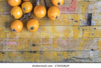 Beautiful rustic image. Fresh loquats, recently recolted from a trea lay on a wooden textured table. Top view