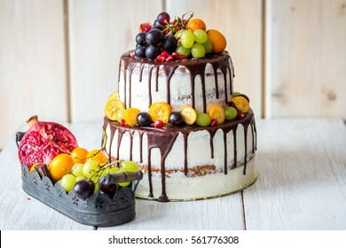Beautiful rustic semi-naked two-tiered cake with chocolate drips and grapes
