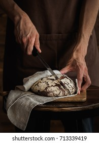 Beautiful Rye bread on a cutting board. Strong bakers hands holding a cutting knife, wooden wall on a background, rustic photography. Vertical photo