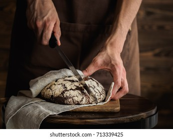Beautiful Rye bread on a cutting board. Strong bakers hands holding a cutting knife, wooden wall on a background, rustic photography