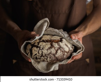 Beautiful Rye bread in a strong bakers hands, wooden wall on a background, rustic photography. horizontal photo close up