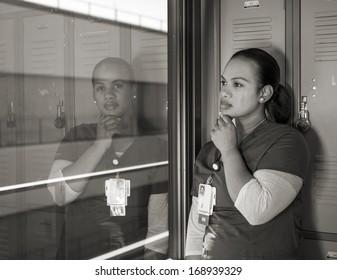 beautiful sad African American nurse crying in a locker room in monochrome