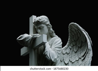 Beautiful sad angel with cross. Fragment of ancient stone statue with a sweet expression that looks down as symbol of unspeakable sadness and death.