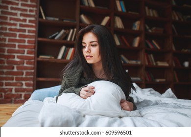 Beautiful sad brunette woman in a green sweater lies on a bed at home