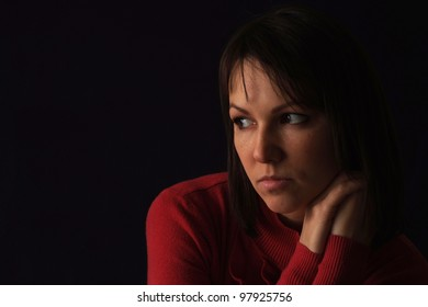 Beautiful sad caucasian woman in red sitting on a black background