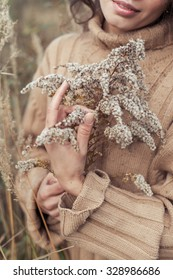 beautiful sad cute attractive woman in a beige sweater wide in a field of dry grass on a cold autumn cloudy day, holding a dry branch, a photo in a beige and coffee tones, chocolate hues
