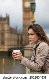 Beautiful sad, depressed or thoughtful young woman in London on Westminster Bridge over the River Thames drinking take out coffee by Big Ben