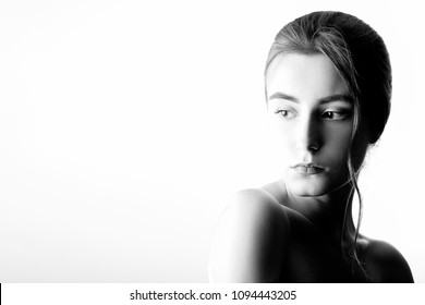 beautiful sad female portrait on white background with copy space, monochrome