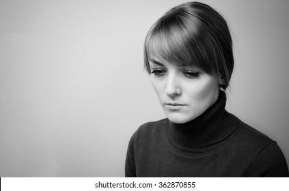Beautiful sad girl with big blue eyes looking down