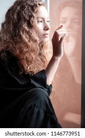 Beautiful sad girl by the window