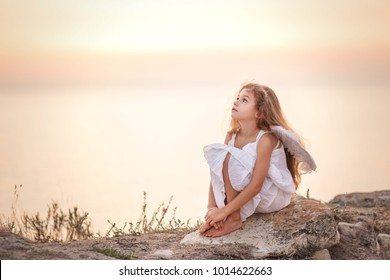 Beautiful sad little angel gir sitting and looking at the sky. Soft focus.