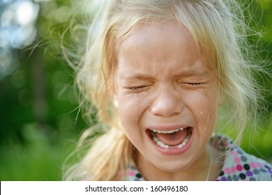 Beautiful sad little girl crying, on summer background.