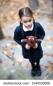 Beautiful sad little girl with with pigtails, dressed in dark blue standing near mystic abandoned building with gothic stairs and holding handmade bear toy. Halloween horror. Loneliness, depression
