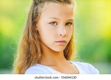 Beautiful sad teenage girl in white blouse, against green of summer park.