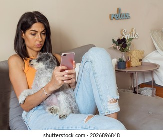 Beautiful Sad Unhappy Young Woman Sitting with her Dog at Home Looking at her Smartphone