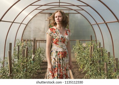 Beautiful sad woman in a dress with print staying in a greenhouse.