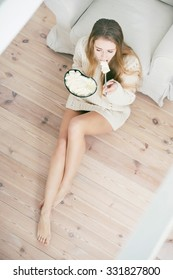 Beautiful sad woman eating ice cream at home.