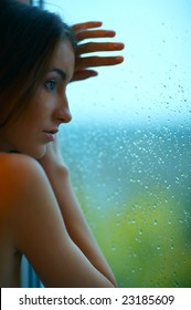 beautiful sad woman stands near the window in rainy day