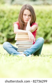 beautiful and sad young student girl sitting on green grass, pile of books under her hands. She is depressed and looking into the camera. Summer or spring green park in background