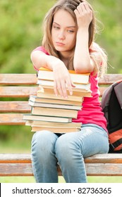 beautiful and sad young student girl sitting on bench with pile of books under her hands. She is depressed and looking away from the camera. Summer or spring green park in background