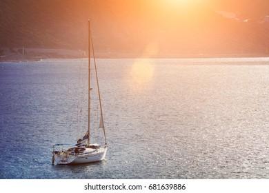 Beautiful sailing boat in the sea at sunrise or sunset