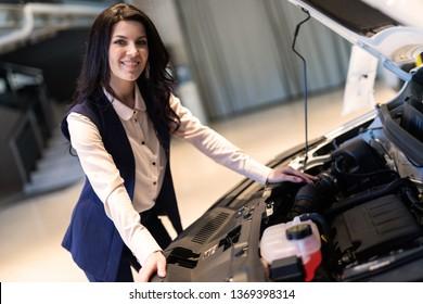 Beautiful sale-manger inspect new car in dealership showroom