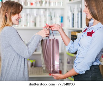 Beautiful saleswoman at beauty store giving shopping bag full of cosmetics to customer