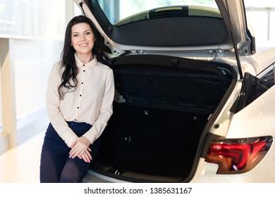 Beautiful saleswoman possing near new car in dealership center