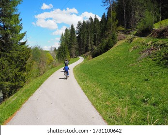Beautiful San Candido-Lienz cycle path. Child on bicycle in nature, Italy