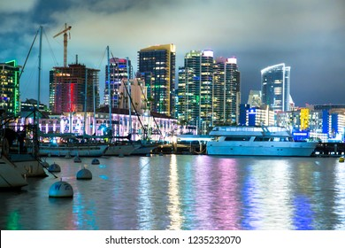 Beautiful San Diego California skyline at harbor seen at night with bay and boats
